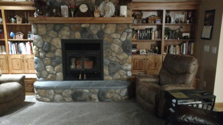 Bricklayer creates stone fireplace